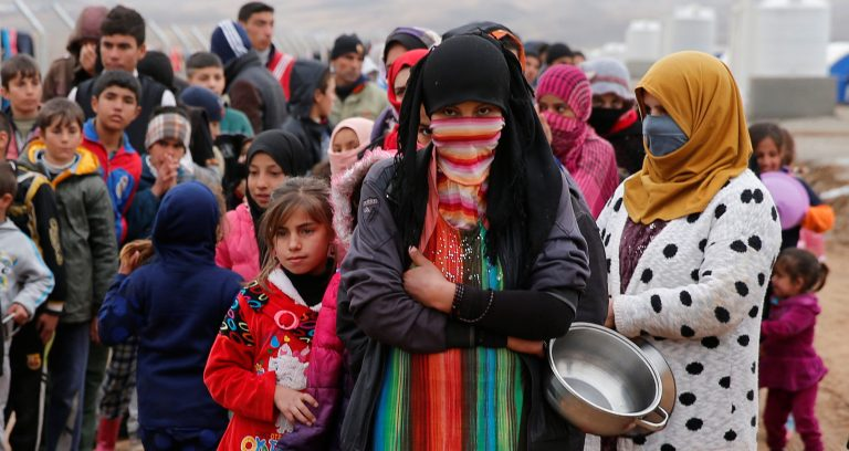 People who fled the Islamic State stronghold of Mosul, stand in line to receive food at a refugee camp, Iraq,December 18, 2016.REUTERS/Ammar Awad - RTX2VJJI