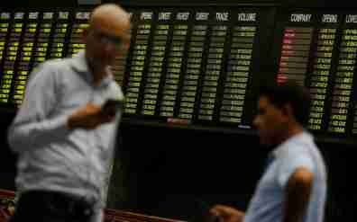 Men use their cell phones as they stand in front of electronic board displaying share market prices during a trading session in the halls of Pakistan Stock Exchange (PSX) in Karachi, Pakistan ?June 12, 2017. REUTERS/Akhtar Soomro - RTS16OE0
