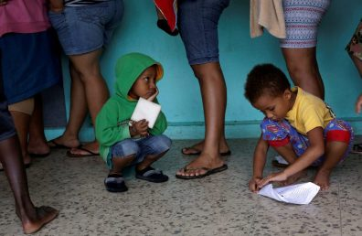 Two children play while their parents line up for clothes at school used as a shelter as storm Otto approaches in Guapiles, Costa Rica November 23, 2016. REUTERS/ Juan Carlos Ulate - RTST0Y6
