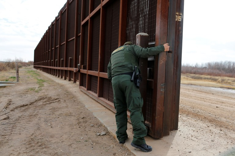 A U.S. Border patrol agent opens a gate on the fence along the Mexico border