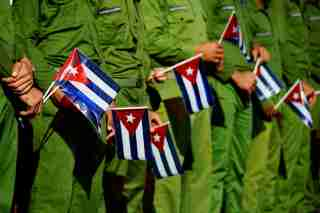 Army soldiers hold Cuban flags. Trump announced new regulations for Cuba on a speech Friday.