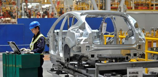 An employee uses a laptop next to a car body at an assembly line at a Ford manufacturing plant in Chongqing municipality April 20, 2012. REUTERS/Stringer CHINA OUT. NO COMMERCIAL OR EDITORIAL SALES IN CHINA - RTS17Y7U