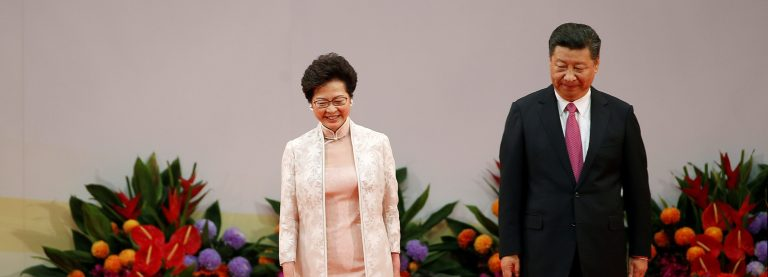 Hong Kong Chief Executive Carrie Lam (L) and Chinese President Xi Jinping walk on the podium after Lam taking oath, during the 20th anniversary of the city's handover from British to Chinese rule, in Hong Kong, China, July 1, 2017. REUTERS/Bobby Yip - RTS19C33