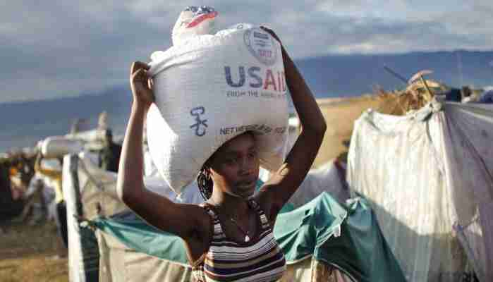 A woman carries a bag of rice from USAID as part of food distributed by various relief agencies in Cite Soleil, Port-au-Prince February 18, 2010. France will provide 270 million euros (US$366.8 million) over two years to Haiti to help the Caribbean nation's economy recover from a devastating January 12 earthquake, France's President Nicolas Sarkozy said on Wednesday. REUTERS/Carlos Barria (HAITI - Tags: DISASTER ENVIRONMENT FOOD SOCIETY POLITICS) - RTR2AI1Z