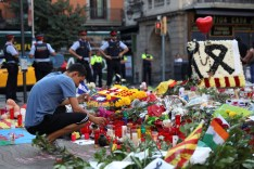 A man lights a candle at an impromptu memorial where a van crashed into pedestrians at Las Ramblas in Barcelona, Spain August 21, 2017. REUTERS/Susana Vera - RTS1CLTL