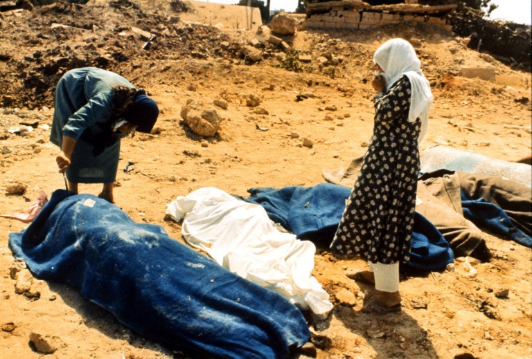 Two women inspect the bodies of the Sabra and Shatila massacre in this
