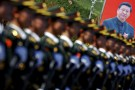 A picture of Chinese President Xi Jinping is seen behind soldiers of China's People's Liberation Army marching during a training session for a military parade to mark the 70th anniversary of the end of the World War Two, at a military base in Beijing, China, August 22, 2015.
