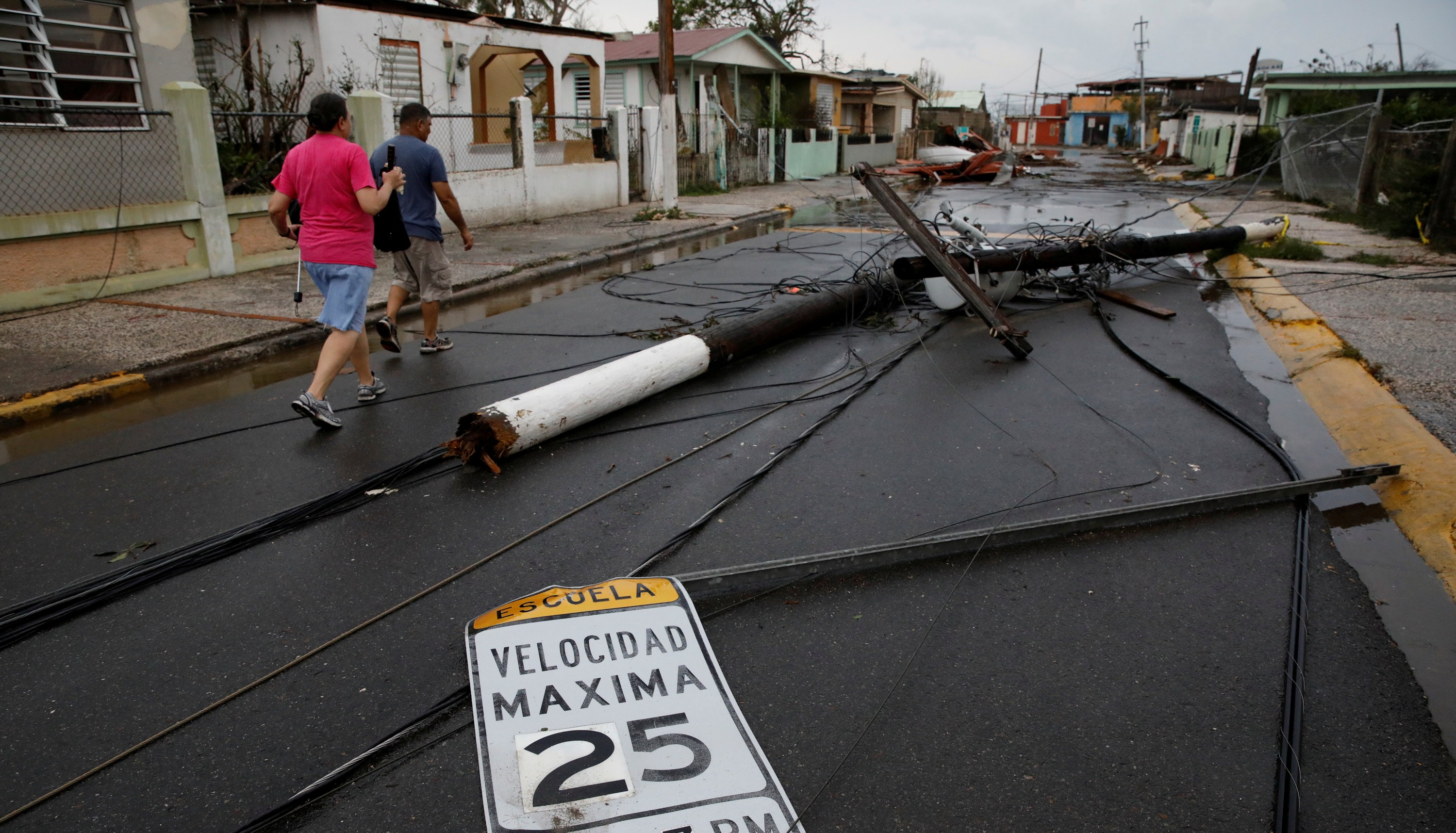 Photo: People walk next to fallen electric poles and traffic sings after the area was hit by Hurricane Maria in Salinas, Puerto Rico, September 21, 2017. REUTERS/Carlos Garcia Rawlins