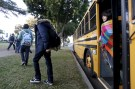 Students exit a bus as they arrive at Venice High School in Los Angeles, California