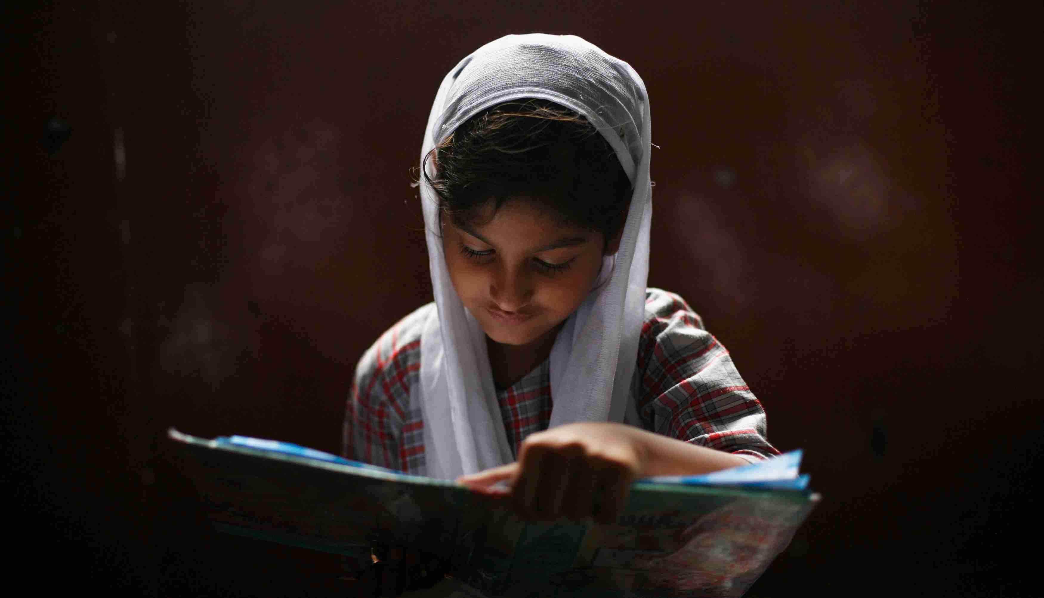 A Muslim girl learns to read the Koran at a madrassa, or religious school, during the holy month of Ramadan in the old quarters of Delhi July 31, 2013. REUTERS/Mansi Thapliyal (INDIA - Tags: RELIGION SOCIETY EDUCATION TPX IMAGES OF THE DAY) - GM1E97V1E3P01