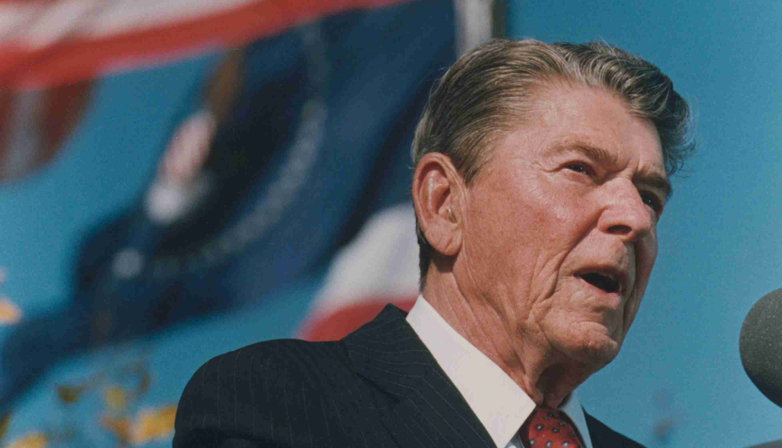 The United States flag flutters behind former President Ronald Reagan.