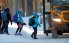 Students board their school bus in a sub-zero temperature.