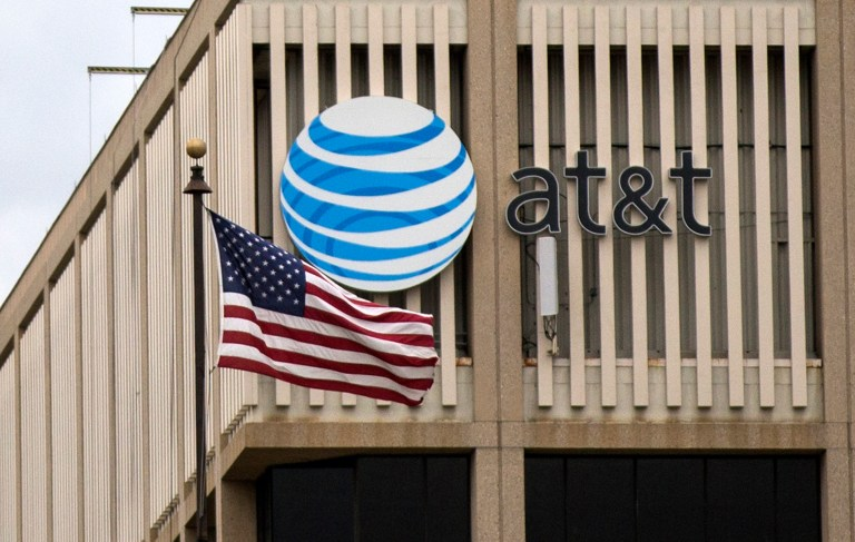 An AT&T Logo is pictured as a U.S. flag flutters in the foreground in Pasadena