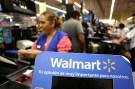 A cashier smiles beyond a Walmart logo.