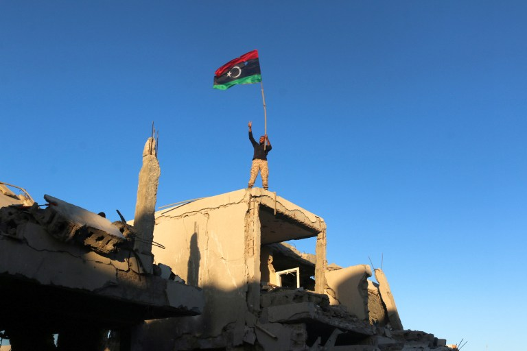 A fighter of Libyan forces allied with the U.N.-backed government waving a Libyan flag flashes victory sign as he stands atop the ruins of a house after forces finished clearing Ghiza Bahriya, the final district of the former Islamic State stronghold of Sirte, Libya December 6, 2016. REUTERS/Hani Amara TPX IMAGES OF THE DAY - RC1FA78AC920