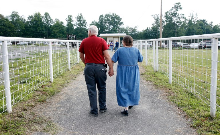 A couple leaves the Remote Area Medical (RAM) health clinic at the Wise County Fairgrounds in Wise, Virginia July 24, 2009. The free clinic, which lasts 2 1/2 days, is the largest of its kind in the nation providing medical, dental and vision services from more than 1,400 medical volunteers. For many residents of this Appalachian area, the RAM clinic serves as the only medical care they may receive each year. REUTERS/Shannon Stapleton (UNITED STATES HEALTH SOCIETY) - GM1E57P0OXR01