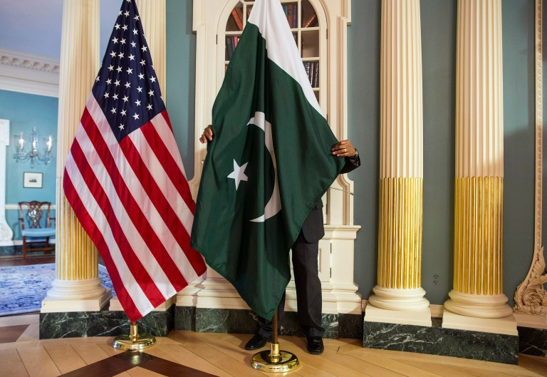 A State Department contractor adjust a Pakistan national flag before a meeting between U.S. Secretary of State John Kerry and Pakistan's Interior Minister Chaudhry Nisar Ali Khan on the sidelines of the White House Summit on Countering Violent Extremism at the State Department in Washington February 19, 2015. REUTERS/Joshua Roberts (UNITED STATES - Tags: POLITICS) - GM1EB2K0EFQ01