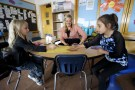 Kyle Schwartz (C), a 3rd grade teacher, works with students Mckylah Lenkiewicz (L) and Juliana Enquist in her classroom at Doull Elementary School in Denver April 17, 2015. Schwartz, who posted notes from her third grade class online and started a social media whirlwind under the hashtag #IWishMyTeacherKnew said on Friday the assignment had been a revelation for her.  REUTERS/Rick Wilking - GF10000063458