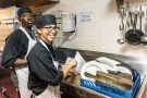 Mature black male dishwasher posing with a young hispanic female dishwasher  at a restaurant kitchen