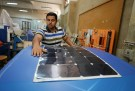 A mechanical engineering student from Helwan University checks the solar-powered vehicle that was designed to help disabled people travel longer distances without assistance, in Cairo, Egypt July 11, 2017. Picture taken July 11, 2017. REUTERS/Mohamed Abd El Ghany - RC1AC552CFA0
