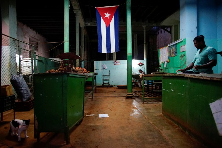"""A Cuban flag decorates a subsidised state store, or """"bodega"""", where Cubans can buy basic products with a ration book they receive annually from the government, in downtown Havana"""