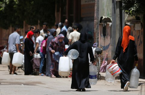 People line up with empty canisters and bottles as they wait to collect filtered water in Toukh, El-Kalubia governorate northeast of Cairo, Egypt June 30, 2017. REUTERS/Amr Abdallah Dalsh - RC15FDCAEB90