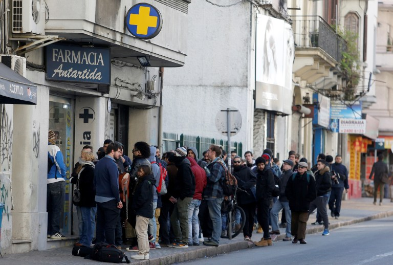 People queue in line outside of a pharmacy to buy legal marijuana in Montevideo