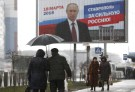 People walk next to the election campaign poster of Russian President Vladimir Putin