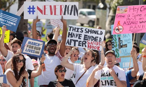 "Students hold signs while rallying in the street during the ""March for Our Lives"" demanding stricter gun control laws at the Miami Beach Senior High School, in Miami, Florida, U.S., March 24, 2018. REUTERS/Javier Galeano - RC1C60279010"