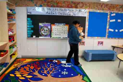 Kindergarten teacher Esenogwas Jacobs tidies her classroom