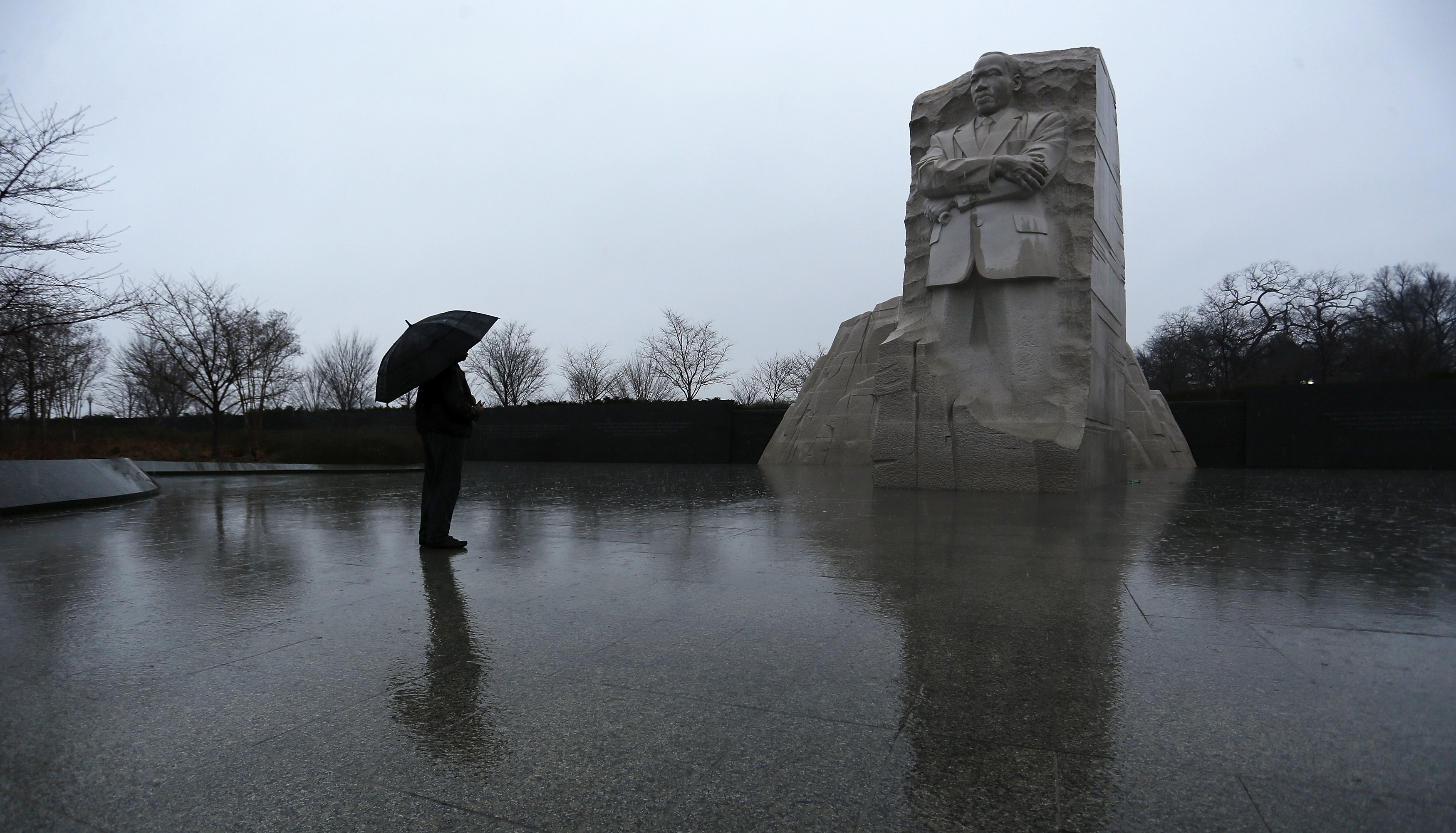 A person stands with an umbrella in a steady rain at the Martin Luther KIng Jr. Memorial in Washington January 18, 2015. REUTERS/Jonathan Ernst