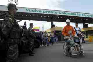 A member of the Colombian civil defense pushes a woman on a wheelchair after she crosses from Venezuela over the Simon Bolivar international bridge.
