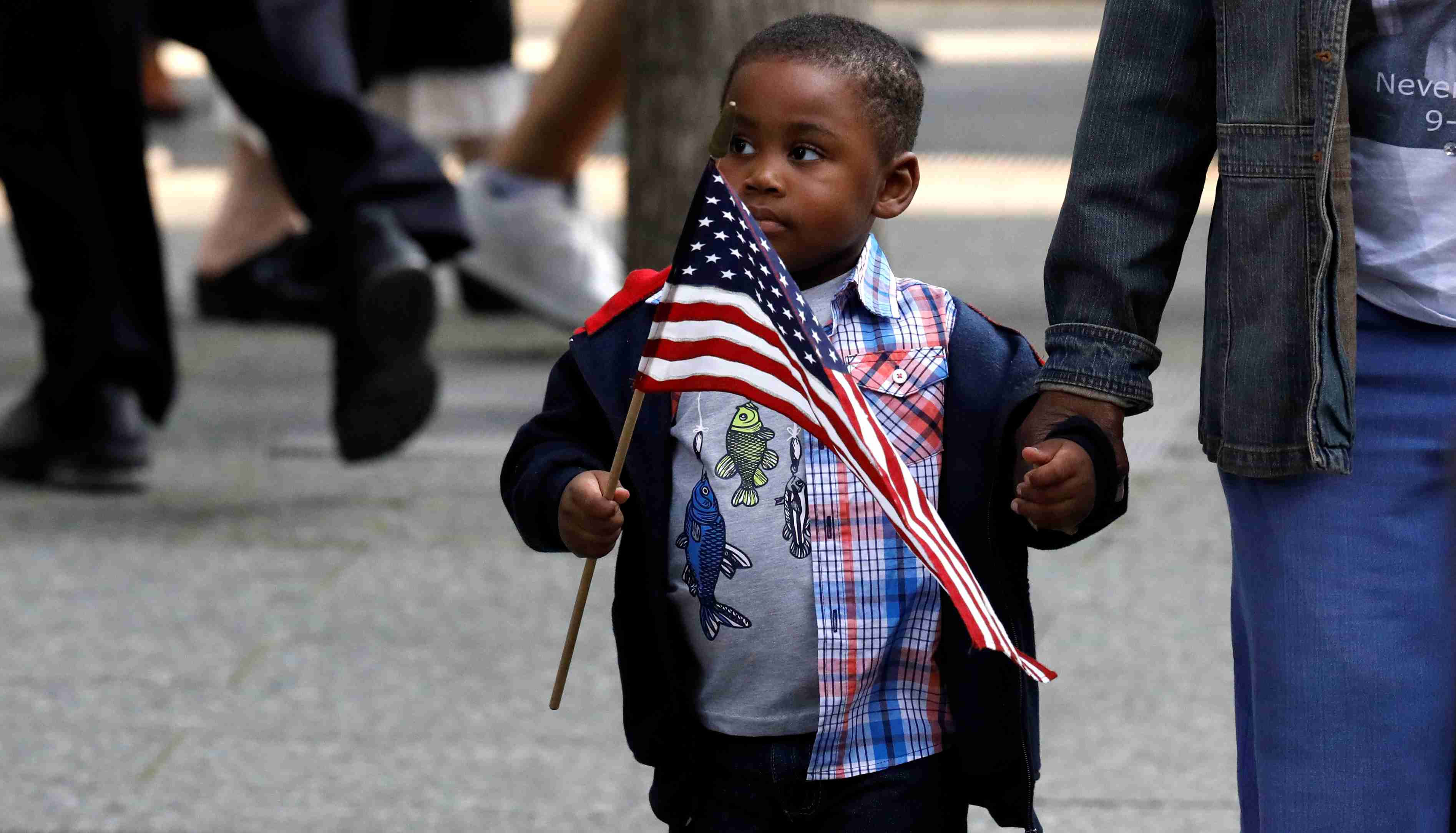 A young boy of color carries an American flag
