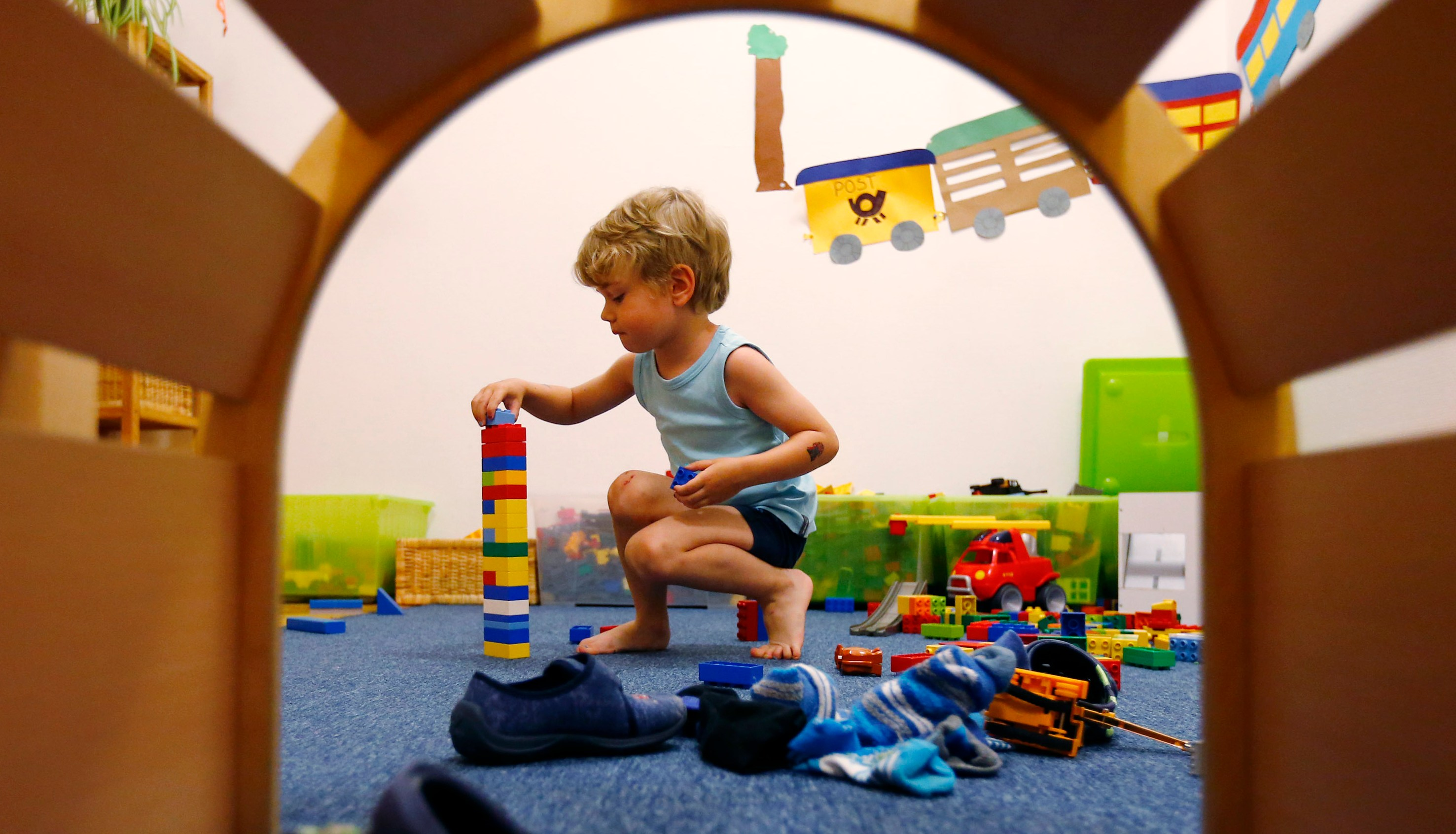 A four year-old boy plays with building blocks