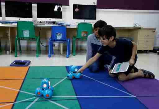 Boys attend a computer programming lesson using robots connected with an application as part of Kcoderz social initiative
