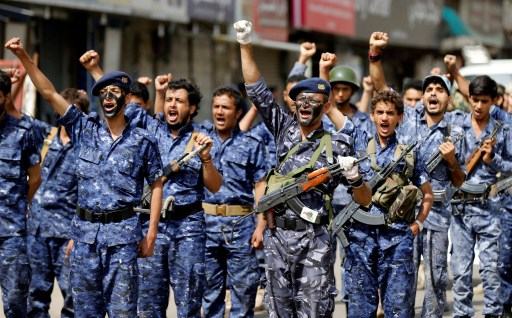 """Members of a security force loyal to the Houthi rebels take part in a military parade at the Tahrir Square in downtown Sanaa, Yemen July 19, 2017. The placard reads: """"Allah is the greatest. Death to America, death to Israel, a curse on the Jews, victory to Islam"""". REUTERS/Khaled Abdullah - RC1C3C220F90"""