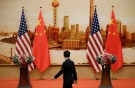 A staff member walks past U.S. and Chinese flags placed for a joint news conference by U.S. Secretary of State Mike Pompeo and Chinese Foreign Minister Wang Yi at the Great Hall of the People in Beijing, China June 14, 2018. REUTERS/Jason Lee - RC13AE41E700