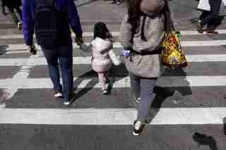 A family holds hands as they cross the street on the first day of Spring in New York, NY, U.S. March 20, 2017. REUTERS/Lucas Jackson - RC1C40DCE220