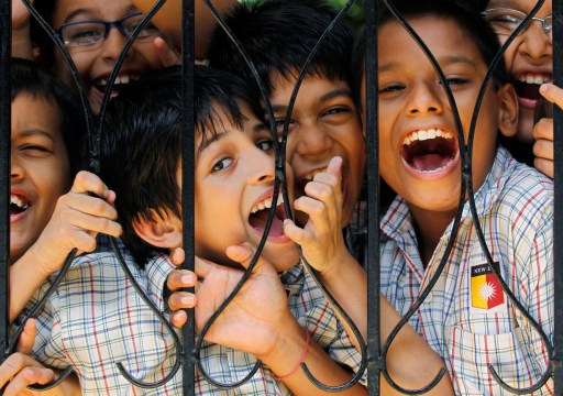 Boys react to the camera during their recess break in the middle of their academic day at a school in Mumbai August 10, 2010. The Right to Education Act that came into force has made free and compulsory education the right of every child between the age of 6 to 14 years old in India. UNESCO says the Act has brought the country closer to meeting its millennium development goals, with an estimated eight million out-of-school Indian children now having better access to education. REUTERS/Danish Siddiqui (INDIA - Tags: EDUCATION) - GM1E68A1UHJ01