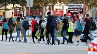 Students cross a street to enter for the first day of classes at Marjory Stoneman Douglas High School in Parkland, Florida, U.S. August 15, 2018.  REUTERS/Joe Skipper - RC1EFE4D0510