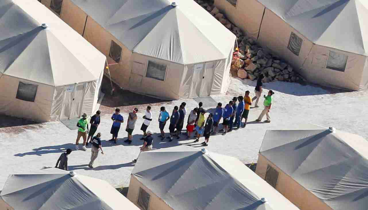 "Immigrant children now housed in a tent encampment under the new ""zero tolerance"" policy by the Trump administration are shown walking in single file at the facility near the Mexican border in Tornillo, Texas, U.S. June 19, 2018.        REUTERS/Mike Blake - RC187D98B970"