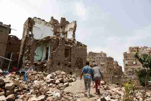 People walk past a house destroyed by an air strike in the old quarter of Sanaa, Yemen August 8, 2018. Picture taken August 8, 2018. REUTERS/Khaled Abdullah