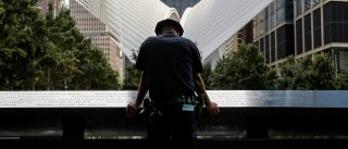 A New York City Police Department (NYPD) officer pauses at the edge of the reflecting pool at the National 9/11 Memorial and Museum during ceremonies marking the 16th anniversary of the attacks in New York, U.S., September 11, 2017. REUTERS/Brendan McDermid     TPX IMAGES OF THE DAY - RC191F4FEB50