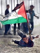 A Palestinian boy holding a Palestinian flag takes shelter from Israeli gunfire during clashes with Israeli soldiers at Gush Kitaf Jewish settlement near Khan-Younes south of the Gaza Strip November 7, 2000.JFL/FMS - RP2DRHYJWXAA