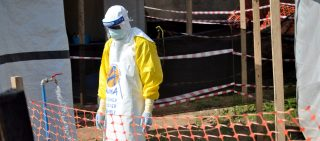 A medical worker wears a protective suit as he prepares to administer Ebola patient care.