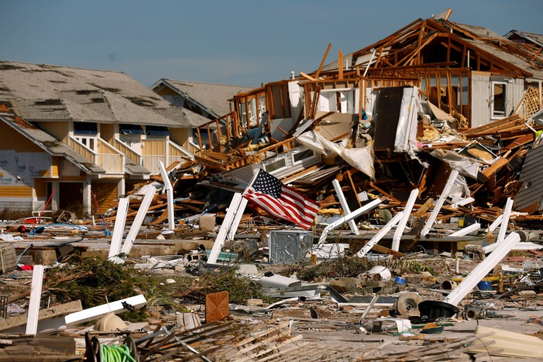 An American flag flies amongst rubble left in the aftermath of Hurricane Michael in Mexico Beach, Florida, U.S. October 11, 2018. REUTERS/Jonathan Bachman TPX IMAGES OF THE DAY - RC13AB293780