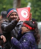A man adjusts a flag for his daughter during celebrations marking the sixth anniversary of Tunisia's 2011 revolution in Habib Bourguiba Avenue in Tunis, Tunisia January 14, 2017. REUTERS/Zoubeir Souissi - RC192ECA71B0