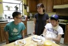 Un Bang (C) spends time with her sons, Shane Bang (L), 21, and Simon Bang (R), 18, at their home in Federal Way, Washington August 8, 2015. With his parents out of work and an office job paying his bills, college junior Shane remembers the anxiety he felt when his younger brother told his family he was headed to University of Washington in the fall. Then they got an unexpected lifeline. A law that took effect last month slashed tuition at public colleges and universities over the next two academic years as much as 20 percent for all Washington students, rich and poor alike. Picture taken August 8, 2015. To match Feature USA-EDUCATION/WASHINGTON      REUTERS/Jason Redmond - GF20000019465