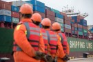 Workers look on as a cargo ship approaches a terminal at the port of Qingdao in Shandong province, China November 8, 2018. REUTERS/Stringer ATTENTION EDITORS - THIS IMAGE WAS PROVIDED BY A THIRD PARTY. CHINA OUT. - RC1BD4412950