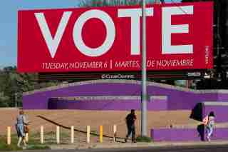 People walk under a billboard encouraging people to vote following the U.S. Midterm elections in Phoenix, Arizona, U.S. November 7, 2018.   REUTERS/Elijah Nouvelage - RC125853C7E0